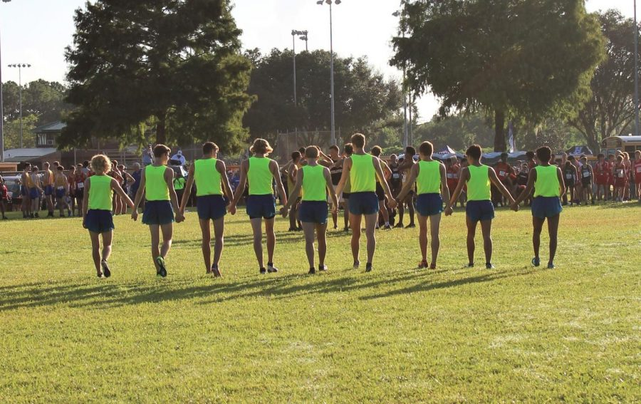 The boys Varsity team joins hands as a sign of unity before each race.