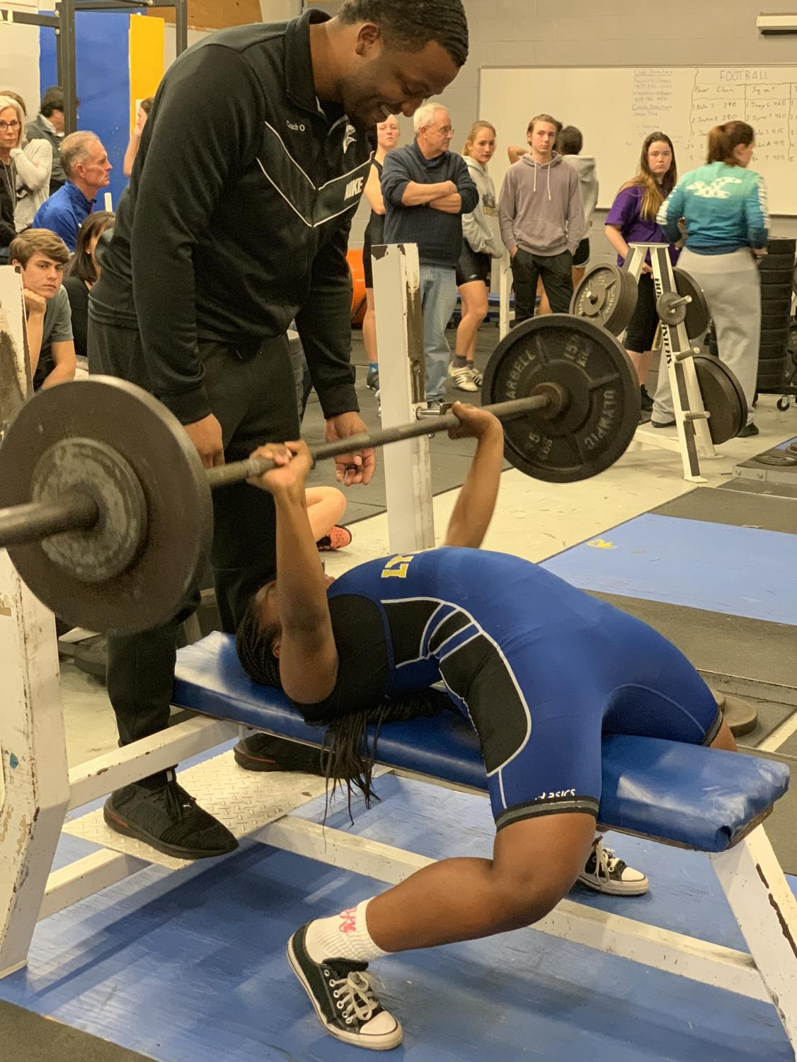 Coach O, one of the girls' weightlifting coaches, smiles excitedly as Bailey Hudson beats her own personal record!